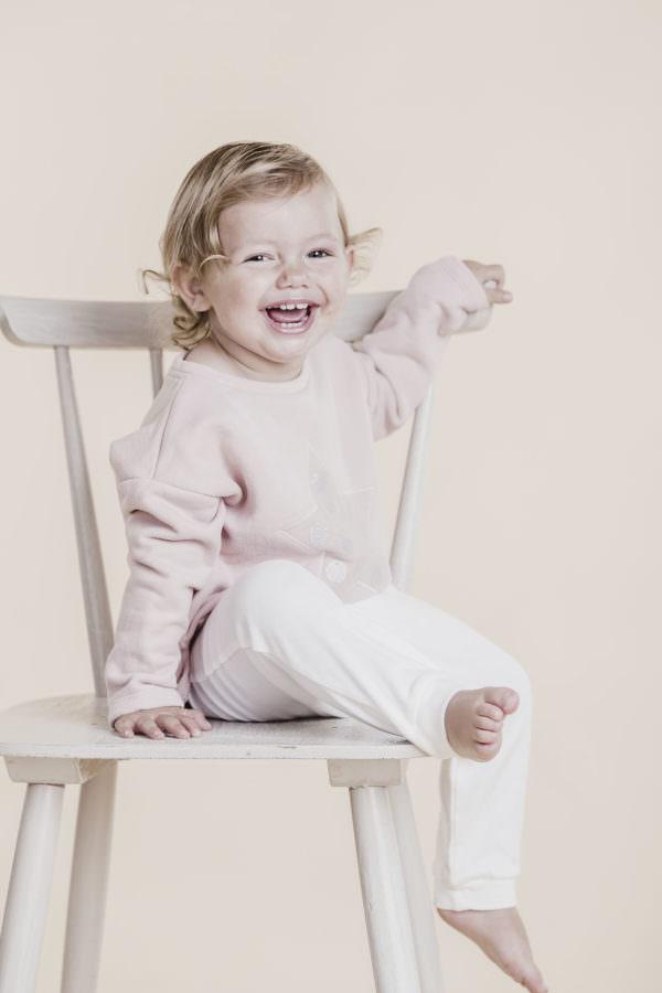 Kindergarten Fotoshooting mit einem kleinen lachenden Mädchen auf einem Stuhl sitzend