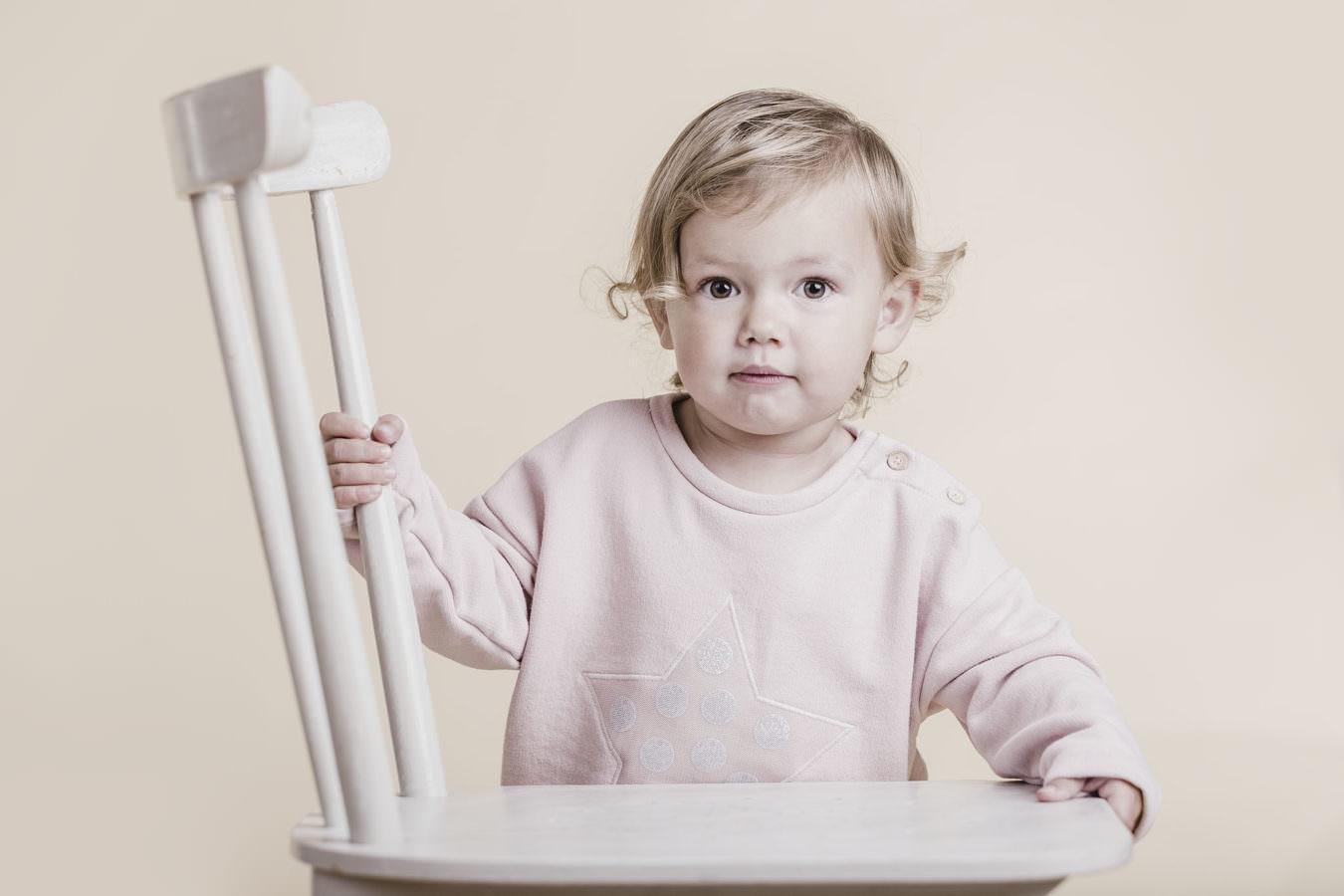 Kindergarten Fotoshooting mit einem kleinen Mädchen, das einen rosanen Pullover trägt