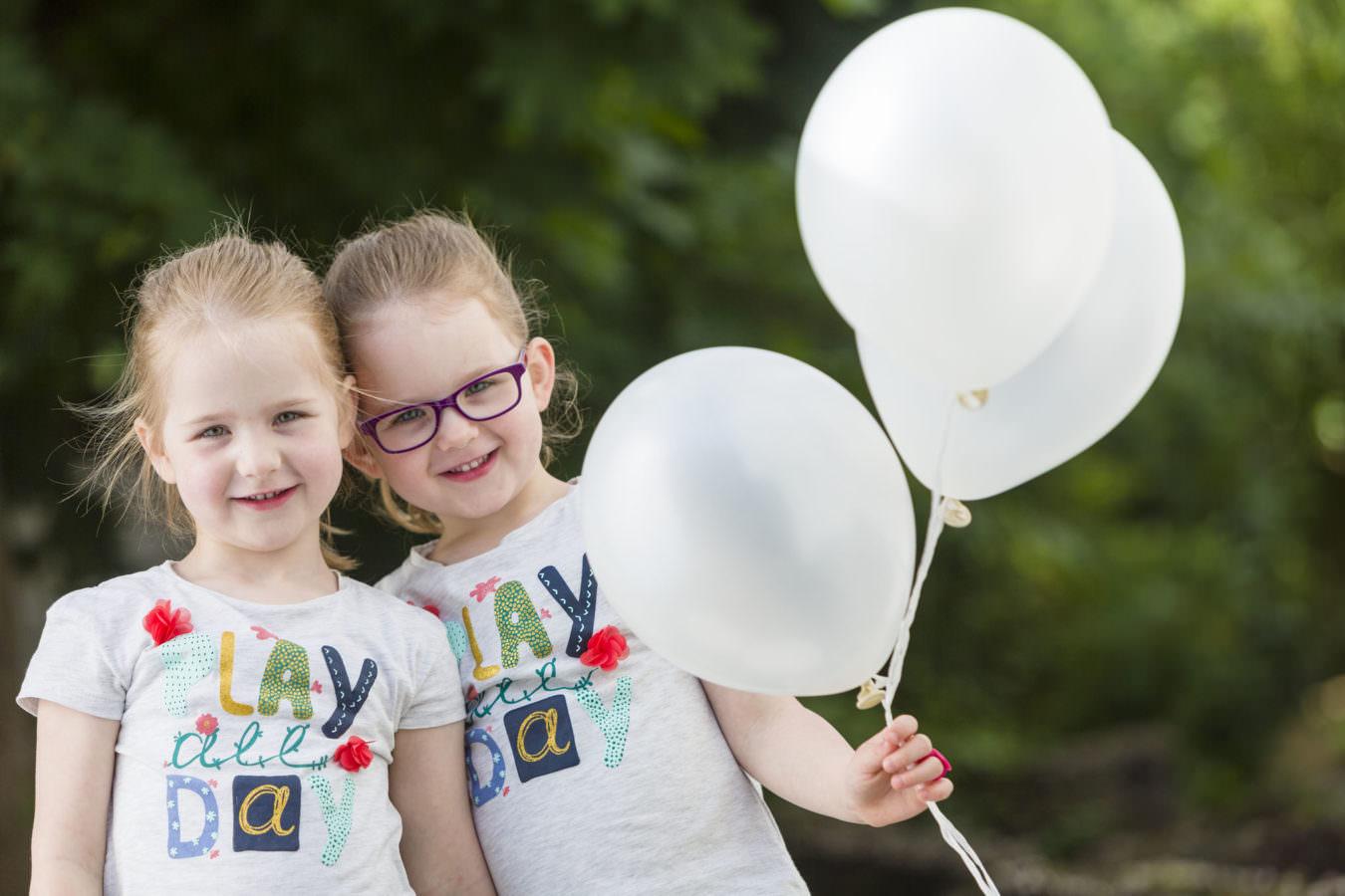 Kita Fotograf hat Zwillinge im Freien, die weiße Ballons halten, abgelichtet