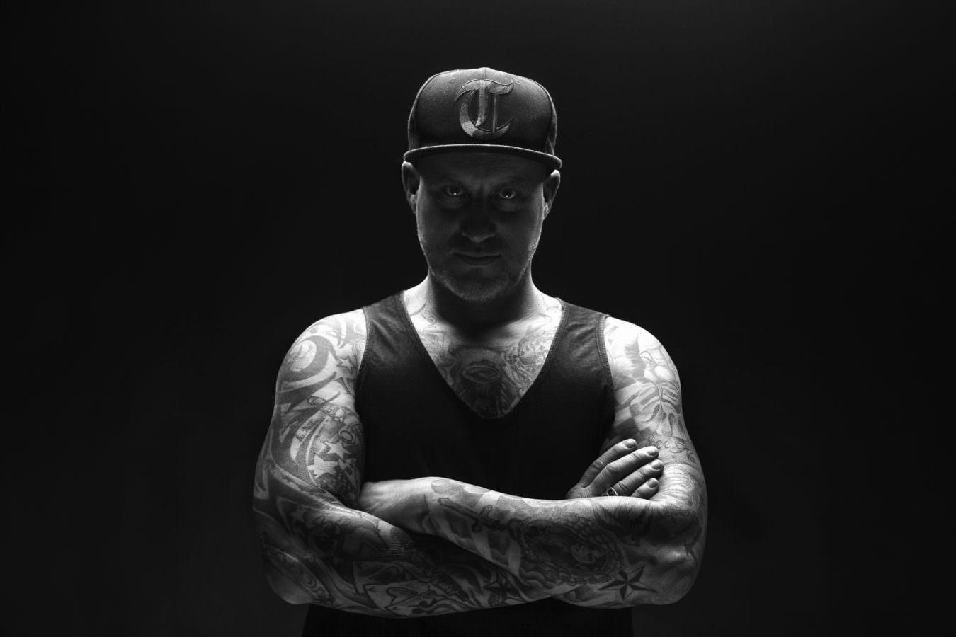 Maenner Fotoshooting im Studio eines Tattowierten vor schwarzem Hintergrund