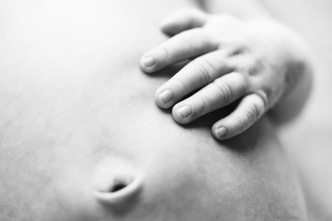 Baby Fotoshooting in Schwarzweiss mit der Hand auf dem Bauch liegend als Detailaufnahme