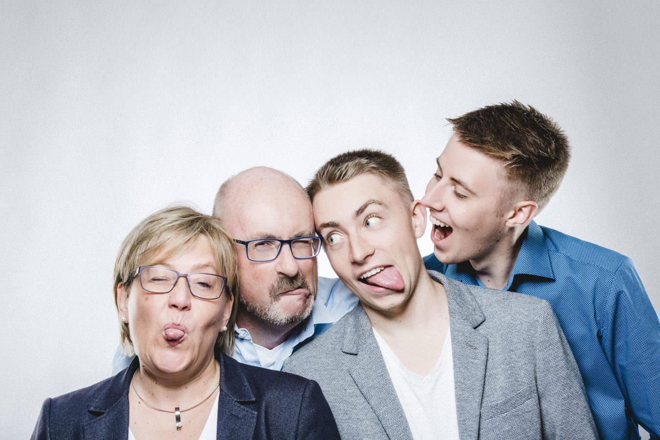 Ein vier Personen Familien Fotoshooting, die im Studio Grimassen schneiden
