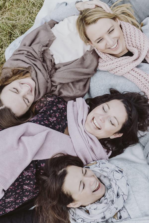 Freundinnen auf dem Boden liegend, die alle herzlich lachen