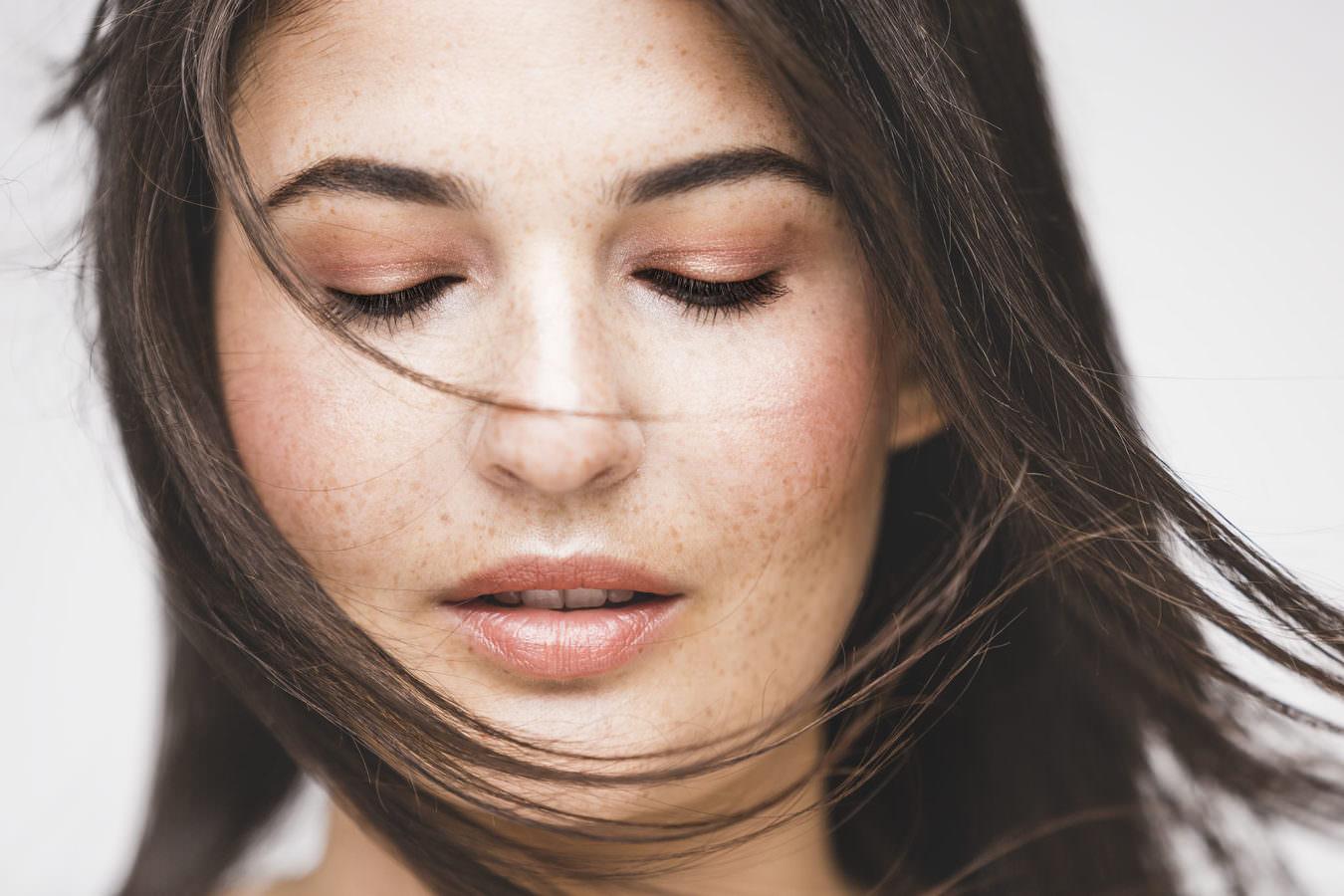 Eine Close Up eines Models mit Sommersprossen, deren Haare über das Gesicht wehen