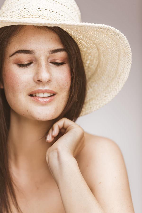 Ein Model mit Sommersprossen und Strohhut auf einer Studiofotografie