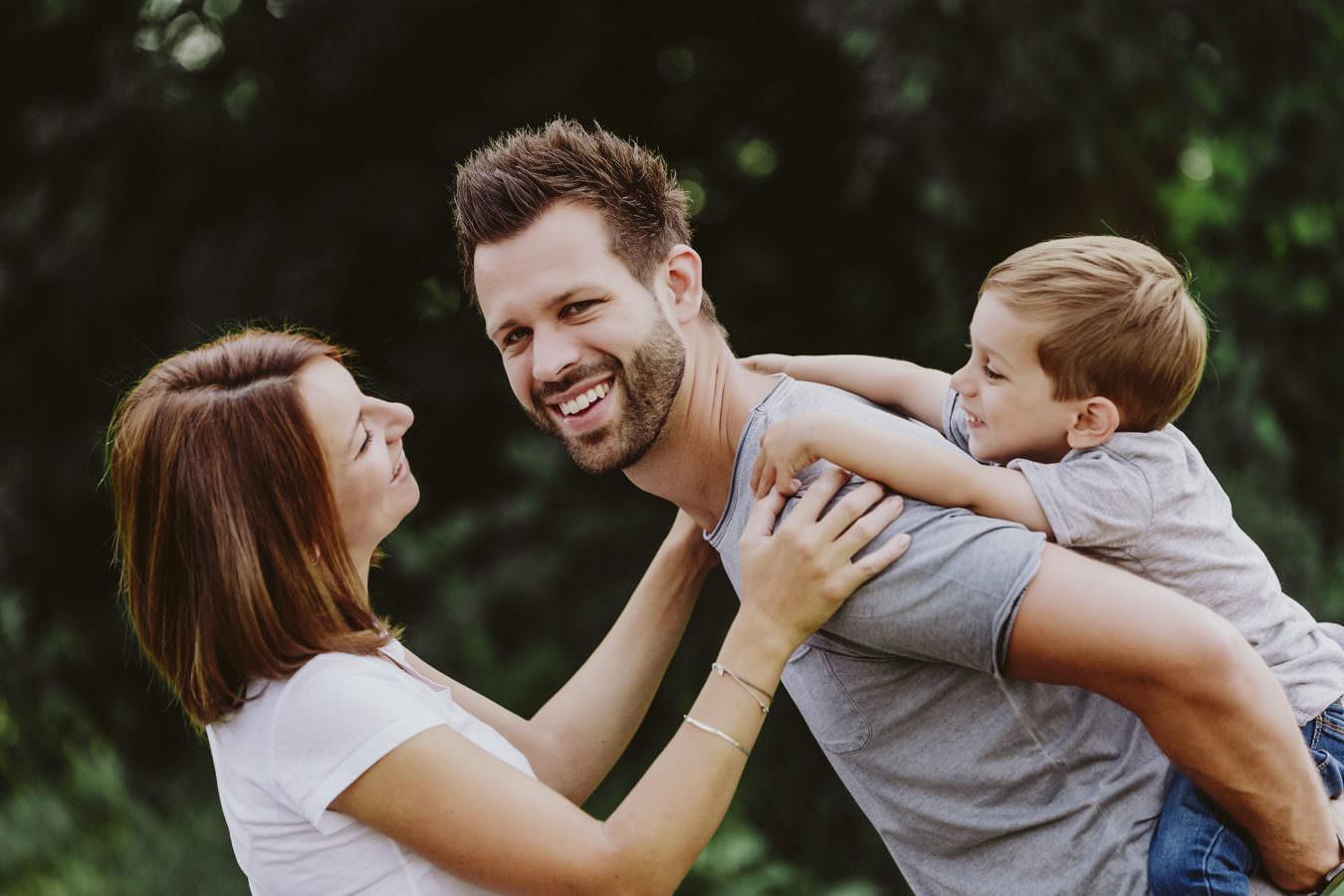 Familien Fotoshooting mit einer lachenden Familie mit Mama, Papa und Sohn auf dem Rücken, die für ein Fotoshooting im Freien stehen