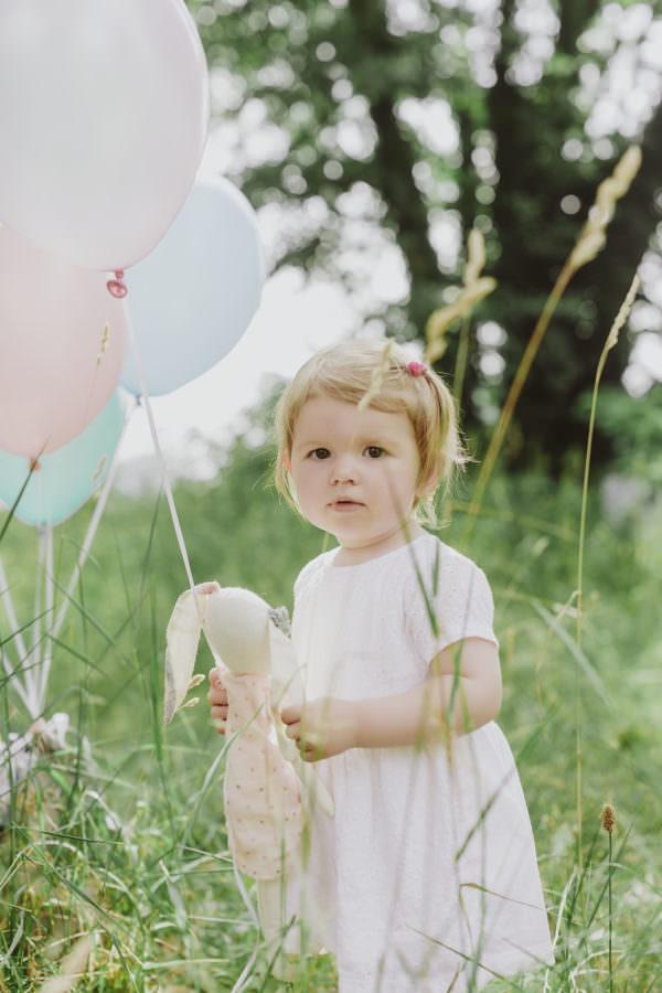 Ein Maedchen mit hellem Kleid und ihrem Schnuffeltier und Ballons auf einer Wiese