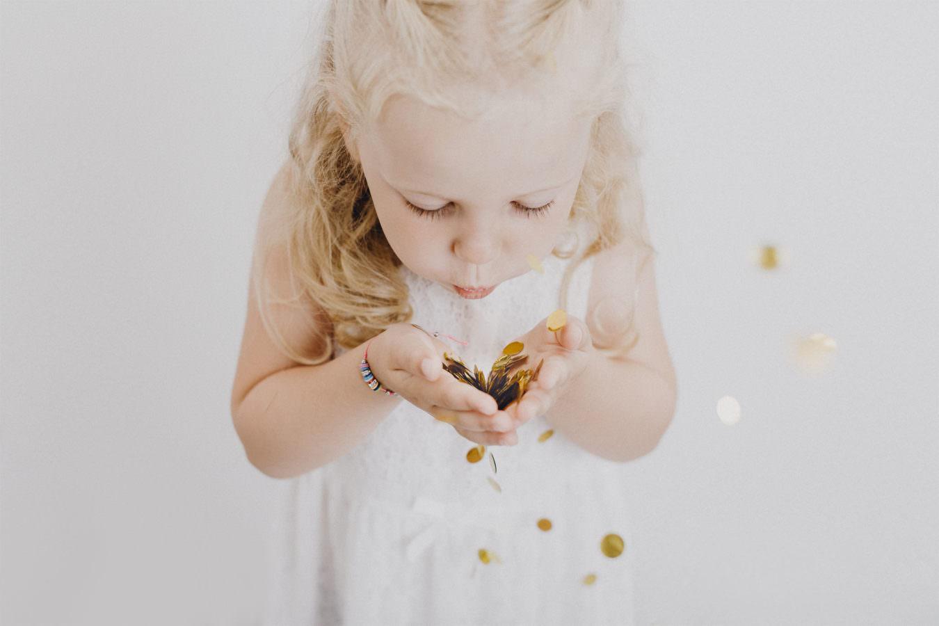Ein blondes Mädchen mit Locken beim Kinder Fotoshooting, das Goldglitzer in die Luft pustet