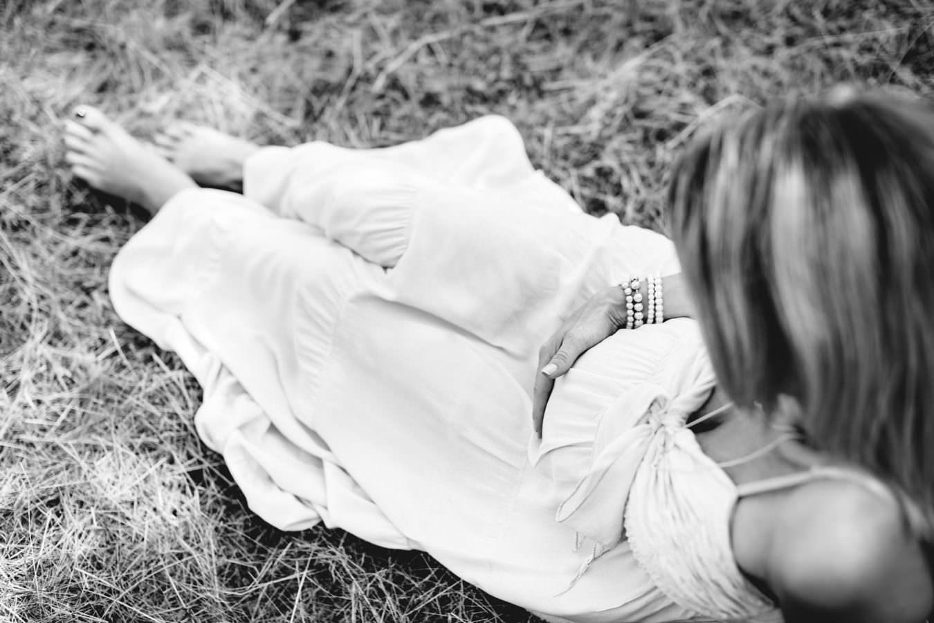 Eine Dame mit Babybauch auf einer Wiese sitzend