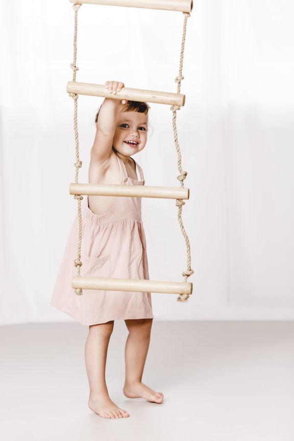 Ein kleines Maedchen fotografiert mit einer Strickleiter im Fotostudio
