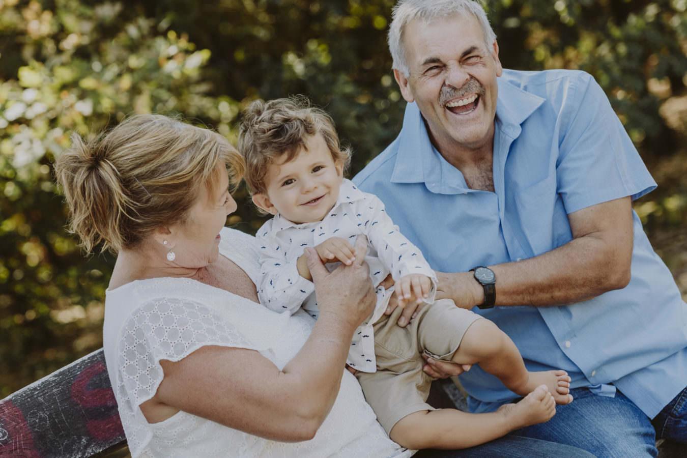 Fotoshooting mit beiden, lachenden Großeltern und ihrem kleinen Enkel