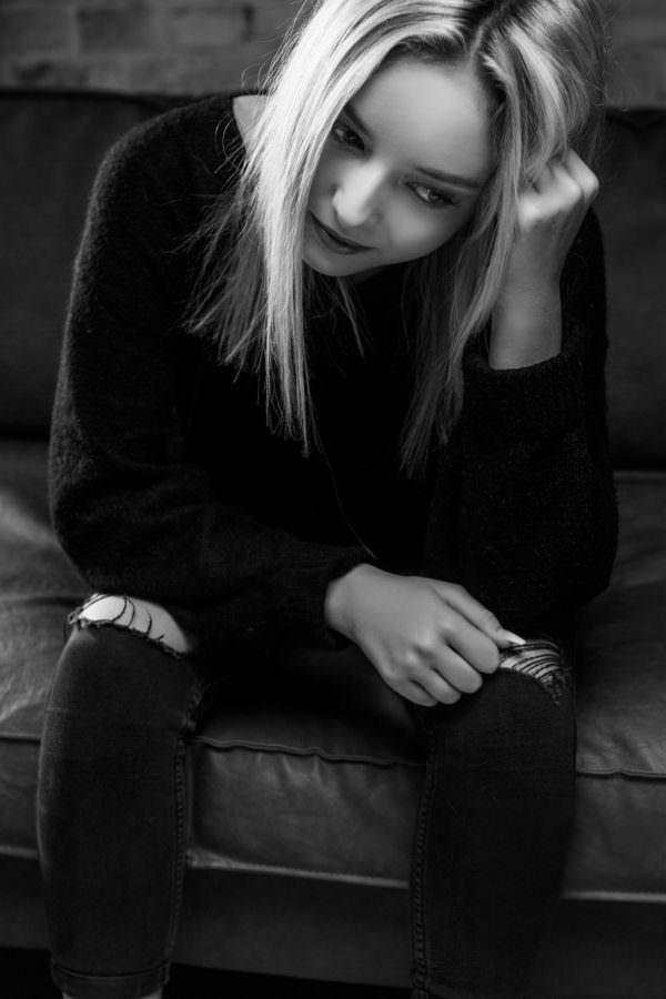 Schwarzweiss Fotografie einer blonden, jungen Dame in Schwarz gekleidet