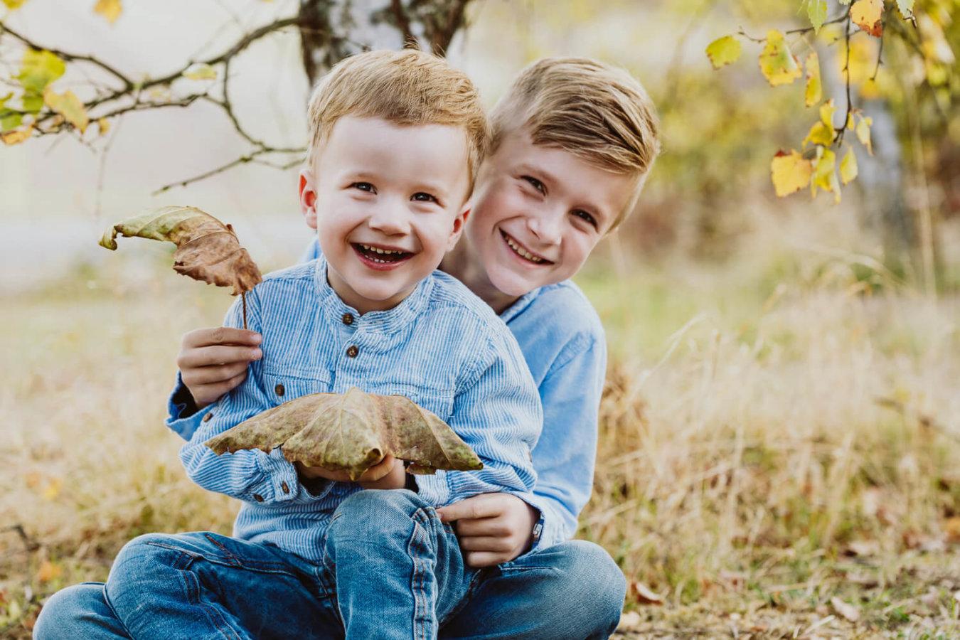 Kita Fotograf mit zwei Jungen im Freien an einem Baum